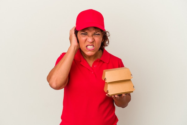 Middle age delivery woman taking burguers isolated on white background covering ears with hands.