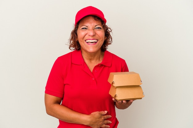 Middle age delivery woman taking burguers isolated on white background laughing and having fun.