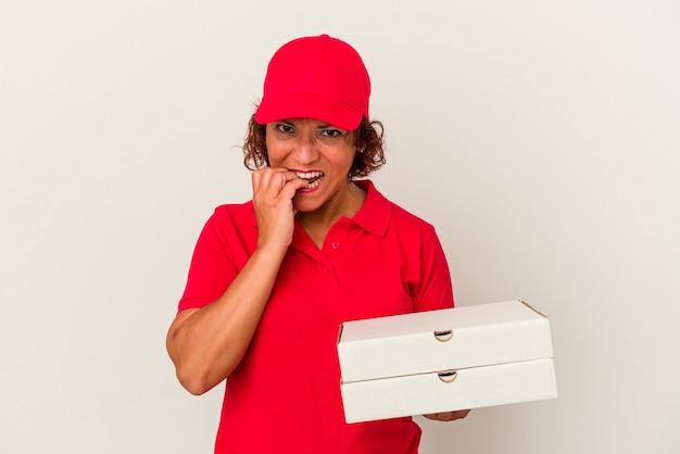 中年の配達の女性は、白い背景で隔離されたピザを爪を噛んで、神経質で非常に心配しています。