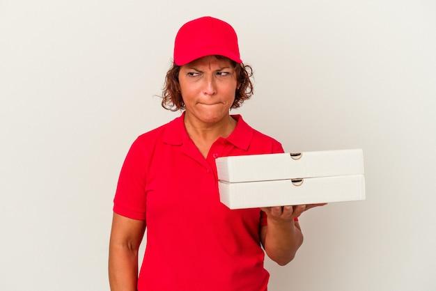 白い背景で隔離のピザを取っている中年の配達の女性は混乱し、疑わしく、不安を感じています。