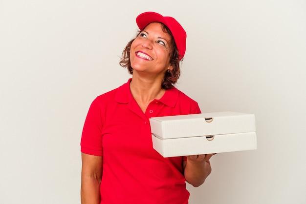 目標と目的を達成することを夢見て白い背景で隔離のピザを取っている中年配達の女性