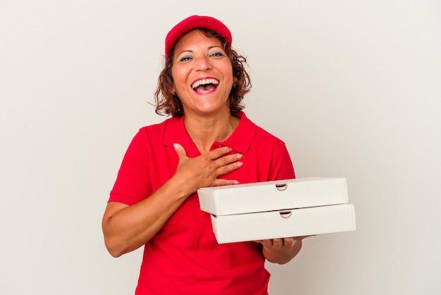 白い背景で隔離のピザを取っている中年配達の女性は、胸に手を置いて大声で笑います。