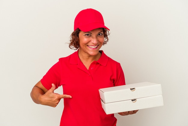 シャツのコピースペースを手で指している白い背景の人に分離されたピザを取っている中年配達の女性、誇りと自信を持って