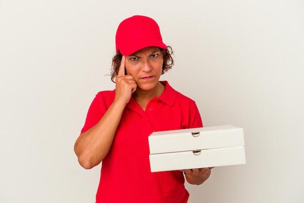 指で寺院を指して、白い背景で隔離のピザを取っている中年配達の女性は、タスクに焦点を当てて考えています。 Premium写真