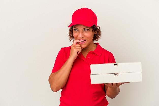 白い背景で隔離のピザを取っている中年配達の女性は、コピースペースを見ている何かについて考えてリラックスしました。