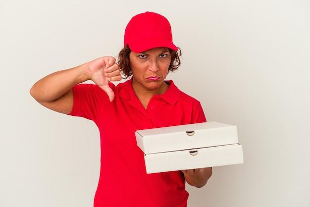 嫌いなジェスチャーを示す白い背景で隔離のピザを取っている中年の配達の女性は、親指を下に向けます。不一致の概念。