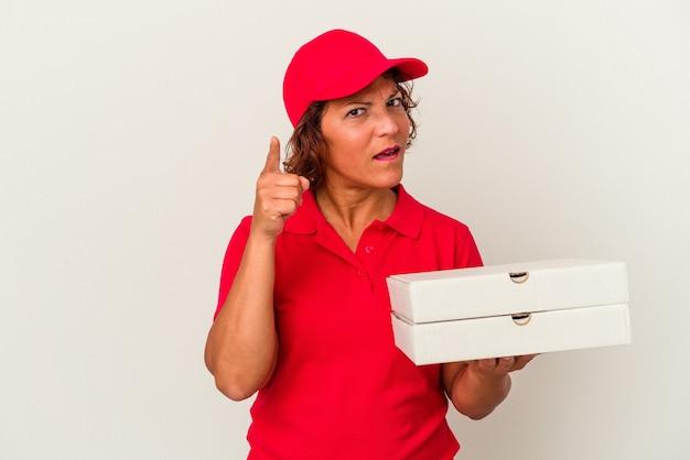 指でナンバーワンを示す白い背景で隔離のピザを取っている中年配達の女性。