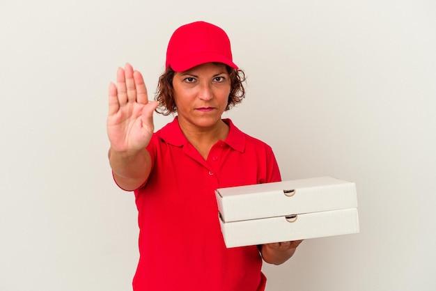一時停止の標識を示す伸ばした手で立っている白い背景で隔離のピザを取っている中年配達の女性は、あなたを防ぎます。 Premium写真