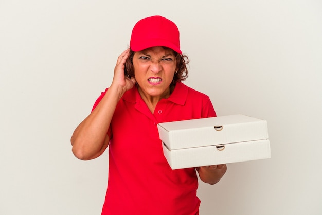 Middle age delivery woman taking pizzas isolated on white background covering ears with hands.