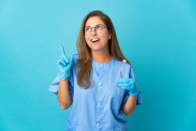 Бразильская женщина-дантист среднего возраста, держащая инструменты над изолированной головой, думает об идее, указывая пальцем вверх