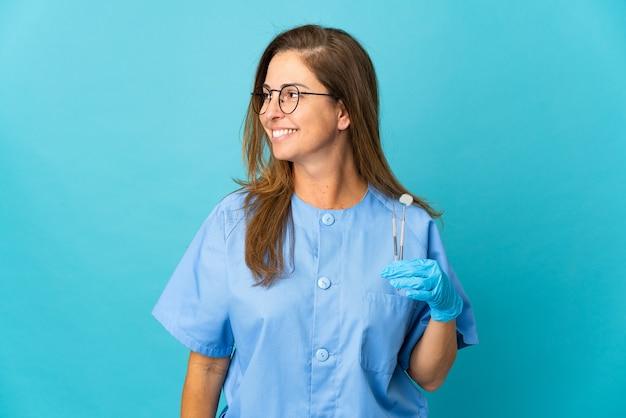 Бразильская женщина-дантист среднего возраста, держащая инструменты над изолированной стеной, смотрящей в сторону
