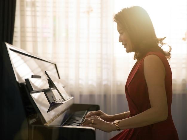 중년의 품위있는 아시아 여성이 행복하게 태블릿 컴퓨터에서 온라인 수업을 통해 피아노를 연주하는 방법을 배우고 새로운 기술을 공부합니다. 아름다운 오렌지 햇살이 뒤쪽 창에서 나옵니다.