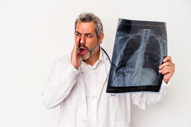 白い背景で隔離のレントゲン写真を保持している中年医師の白人男性は、秘密のホットブレーキニュースを言って脇を見ています