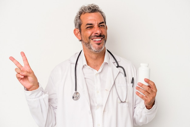指で平和のシンボルを示すうれしそうなのんきな白い背景に分離された中年医師の白人男性。