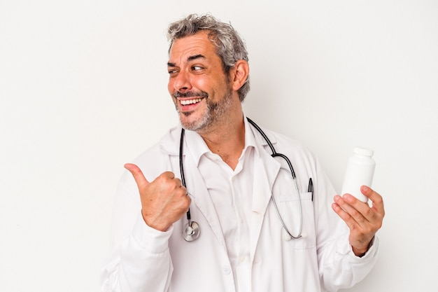 Middle age doctor caucasian man isolated on white background  points with thumb finger away, laughing and carefree.