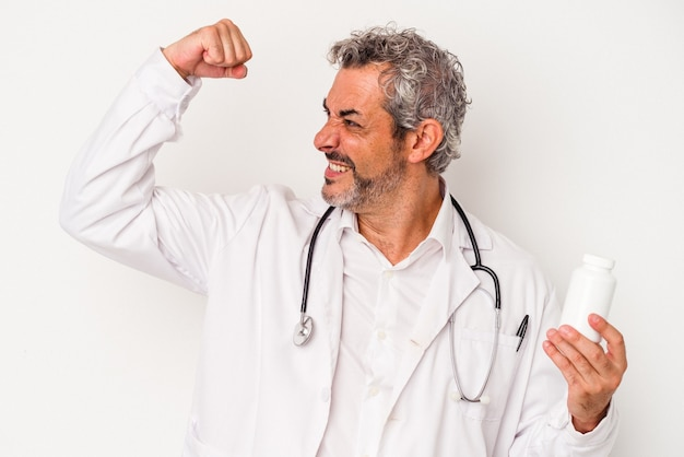 Middle age doctor caucasian man isolated on white background  raising fist after a victory, winner concept.