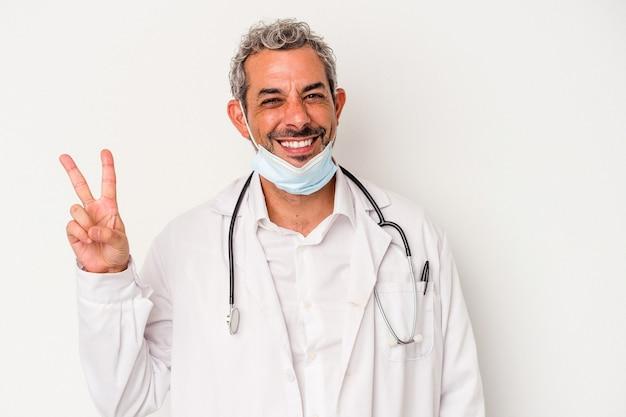 白い背景に分離されたウイルスのマスクを身に着けている中世の医者の男は、指で平和のシンボルを喜んで気楽に示しています。