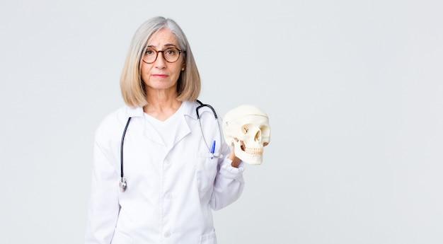 頭蓋骨を保持している中年の医者の女性