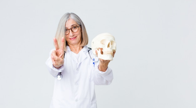 Middle age  doctor woman holding a skull