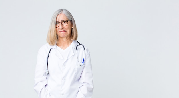 Middle age doctor woman looking puzzled and confused, biting lip with a nervous gesture, not knowing the answer to the problem