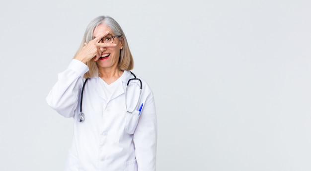 Middle age doctor woman looking shocked, scared or terrified, covering face with hand and peeking between fingers