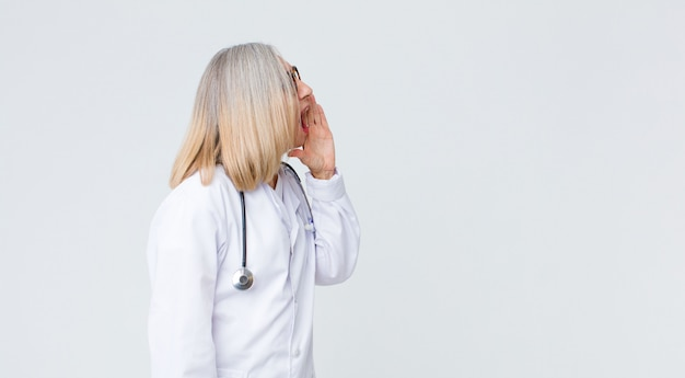 Middle age doctor woman profile view, looking happy and excited, shouting and calling on the side