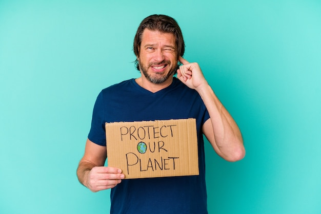 手で耳を覆う青い背景に分離された私たちの惑星のプラカードを保護する中年のオランダ人。