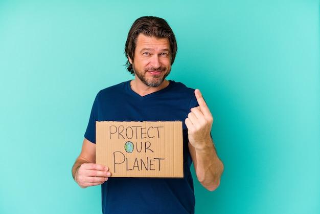 青い背景に隔離された私たちの惑星のプラカードを持っている中年のオランダ人は、招待が近づくようにあなたに指を指しています。