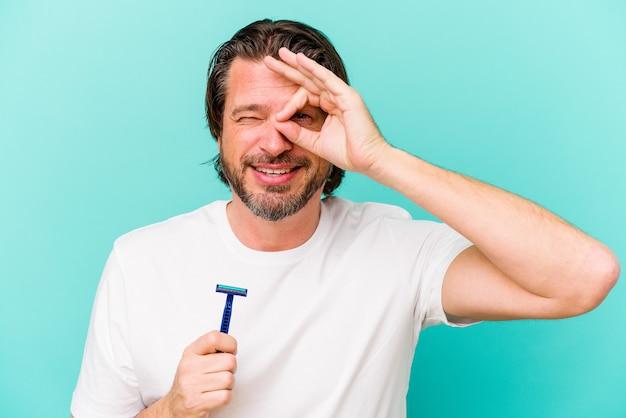 青い背景に分離されたかみそりの刃を保持している中年のオランダ人は、目に大丈夫なジェスチャーを維持して興奮しました。