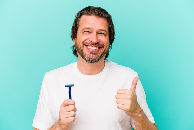 笑顔と親指を上げて青い背景で隔離かみそりの刃を保持している中年のオランダ人