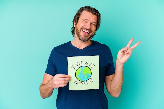 파란색 벽에 고립 된 행성 b 현수막을 들고 중년 네덜란드 남자는 손가락으로 평화의 상징을 보여주는 즐겁고 평온한