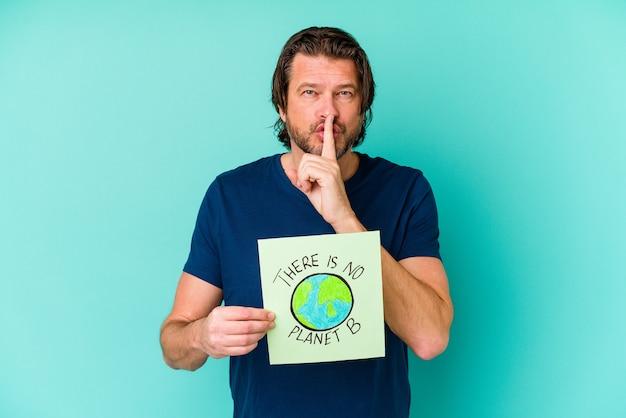 Голландский мужчина средних лет, держащий в руках не планету b, изолированную на синей стене, хранящую в секрете или просящую о тишине.