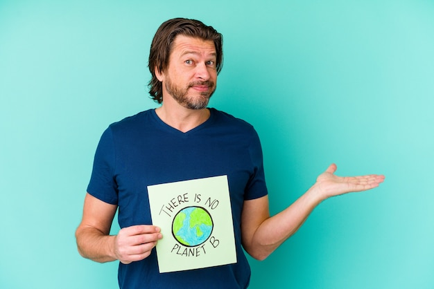 중년 네덜란드 남자는 손바닥에 복사 공간을 표시하고 허리에 다른 손을 잡고 파란색에 행성 b 플래 카드가 없습니다.