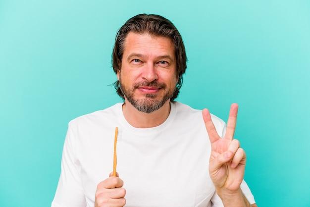 青い背景に分離された歯ブラシを持っている中年のオランダ人は、指で5番を示して陽気に笑っています。