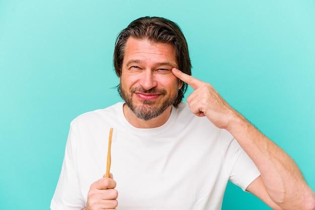 人差し指で失望のジェスチャーを示す青い壁に隔離された歯ブラシを保持している中年のオランダ人。