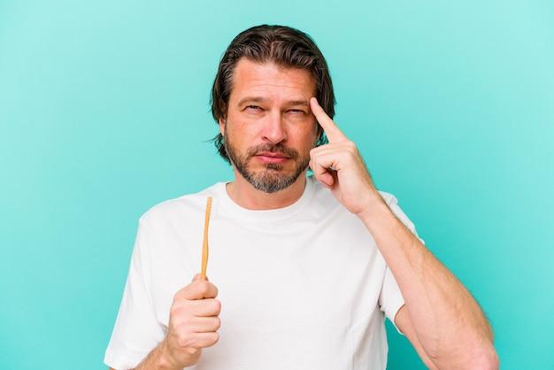 Голландский мужчина средних лет, держащий зубную щетку на синем указывающем виске пальцем, думая, сосредоточился на задаче.