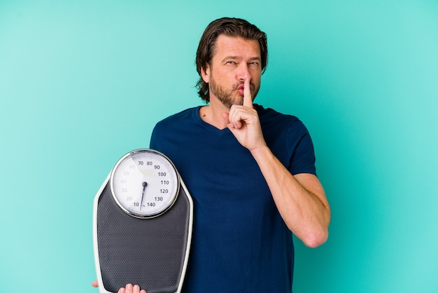 Middle age dutch man holding a scale on blue keeping a secret or asking for silence.