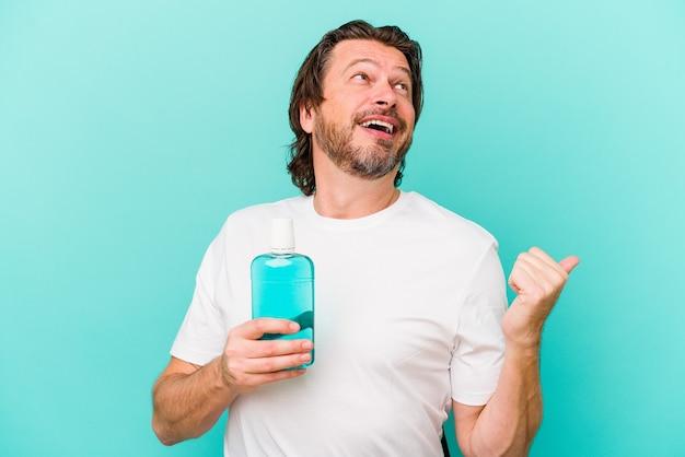 青い背景のポイントで隔離されたうがい薬を持って座っている中年のオランダ人は、親指の指を離れて、笑ってのんきです。
