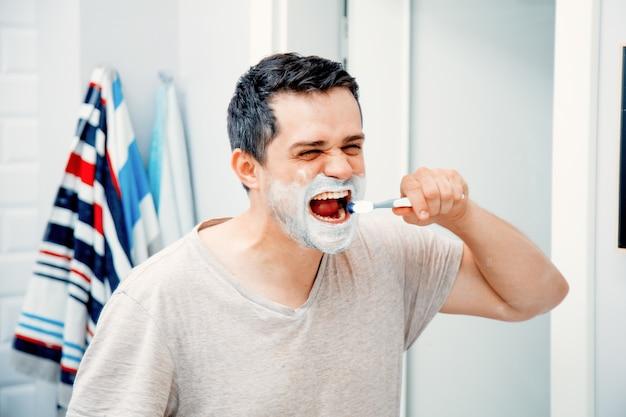 Отец среднего возраста чистит зуб утром в ванной