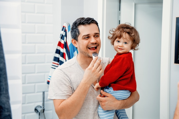 유아 태양을 들고 화장실에서 아침에 면도하는 중년 아버지