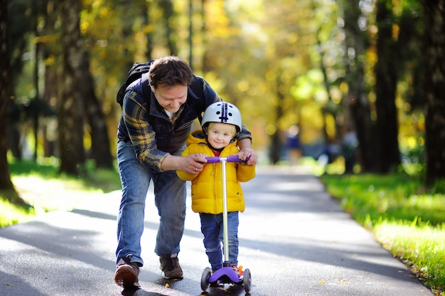 Middle age father showing his toddler son how to ride a scooter in a autumn park
