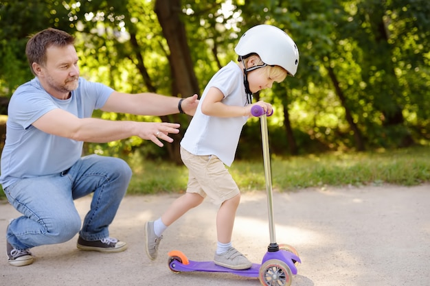 Middle age father showing his toddler son how to ride a scooter in summer park.