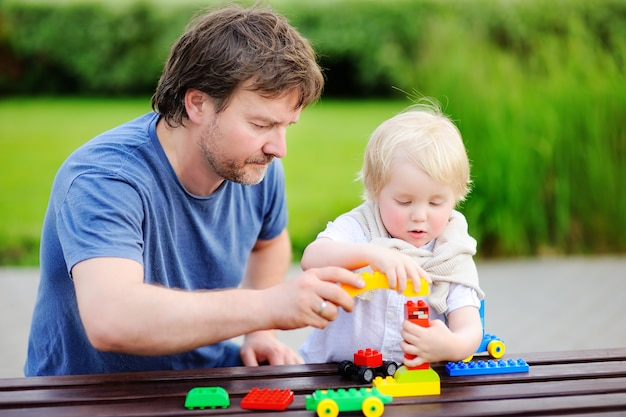 Middle age father with his toddler son playing with colorful plastic blocks