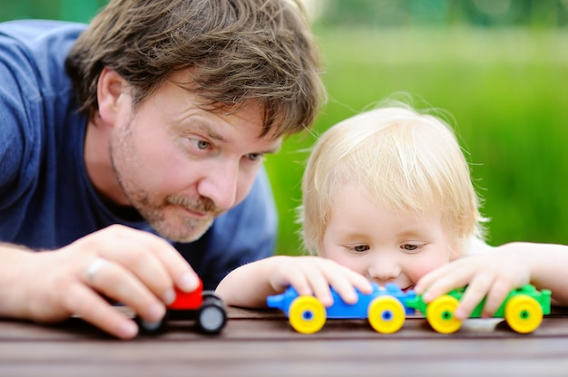 Middle age father with his toddler son playing with toy trains outdoors.