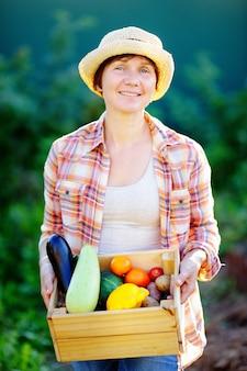 Садовница среднего возраста держит деревянный ящик со свежими органическими овощами с фермы
