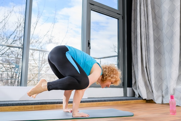 Женщина среднего возраста подходит для стойки на руках на коврике и удерживает тело, упражнения для фитнеса
