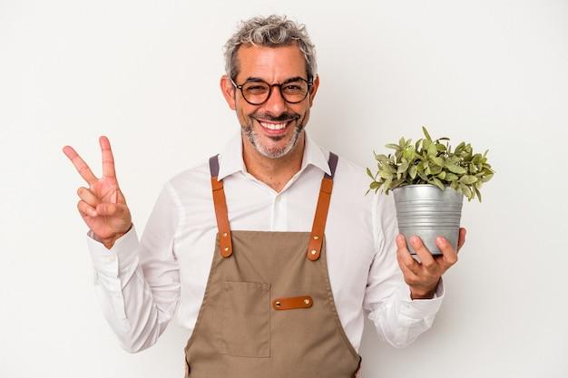 흰색 배경에 격리된 식물을 들고 있는 중년 정원사 백인 남자는 손가락으로 평화 상징을 보여주는 즐겁고 평온합니다.