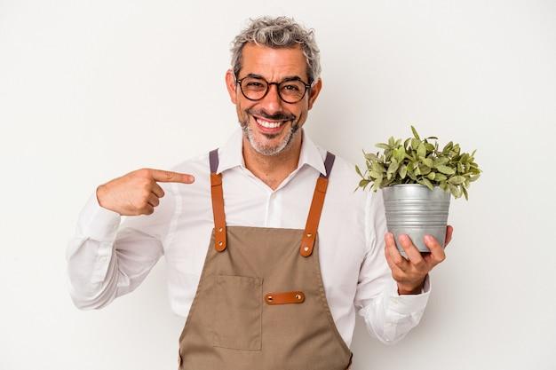 흰색 배경에 격리된 식물을 들고 있는 중년 정원사 백인 남자가 자랑스럽고 자신감 있는 셔츠 복사 공간을 손으로 가리키는 사람