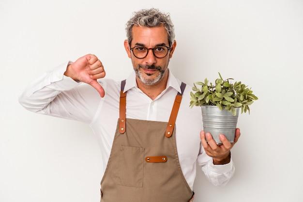 흰색 배경에 격리된 식물을 들고 있는 중년 정원사 백인 남자는 싫어한다는 제스처를 보이고 엄지손가락을 아래로 내립니다. 불일치 개념입니다.