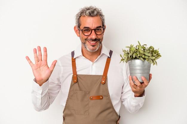 흰색 배경에 격리된 식물을 들고 있는 중년 정원사 백인 남자는 손가락으로 5번을 보여주며 밝게 웃고 있습니다.